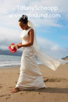 Picture of a bride with flowers waling along the ocean beach. The Bride is wearing her wedding dress, all white of course, and she has a bouquet of white and red flowers in her hands. African american bride walking on the sand at the beach.