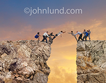 Ten business people bridge a gap with team work as they use their bodies for form a bridge over a deep chasm in a metaphor for teamwork, success and challenge.