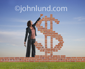 In this photograph a woman places a brick on a dollar sign as she builds her brick and mortar small business.