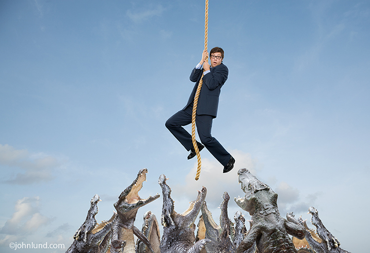 Crocodiles snap at a businessman hanging at the end of his rope in this humorous stock photo about risk, danger and challenge.