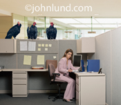 Doom, gloom and failure is the topic of this photo of a woman in her office with vultures perched ominously on the cubicle walls.