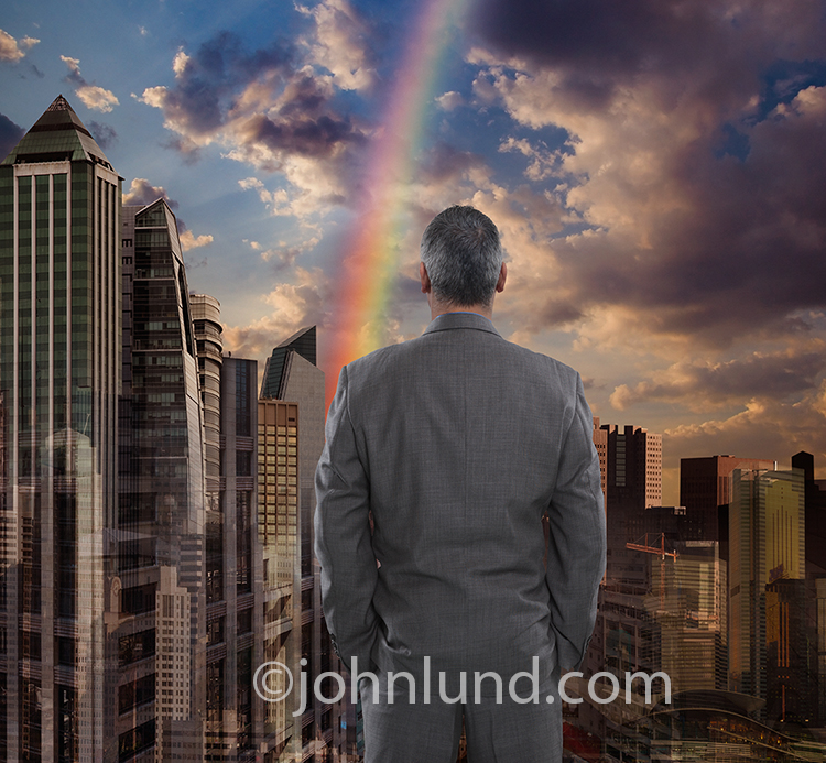 A businessman looks out over a city skyline with a rainbow leading to success in an urban environment.