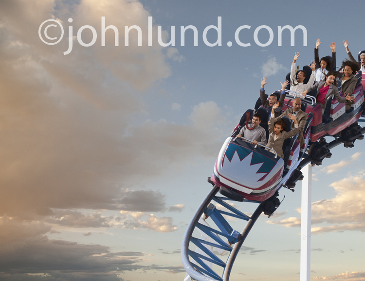 A funny stock photo shows terrified business people riding a roller coaster illustrating the wildly gyrating markets, economy and business climate.