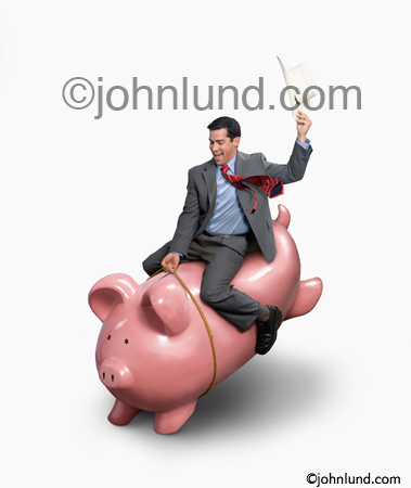 Stock photo of a businessman riding a bucking piggy bank illustrating the concept of volatility, the ups and downs, of the financial, investing, and capital markets.