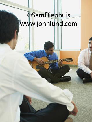 Picture of nicely dressed men n dress shirts and ties sitting on the floor of an empty room and one is playing the guitar. Office workers playing the guitar in an empty office. Pics of co-workers bonding. Ad pics.