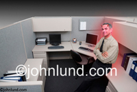 Stock photo of a business man in a cubicle with devil horns and a red glow symbolizing the darker side of business.