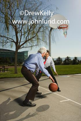 Stock photo of two Hispanic, Mexican, or Latino businessmen playing basketball outdoors in the sun. Part of an active healthy lifestyle. A senior executive dribbling the basketball in a dress shirt and tie. Ad pics.