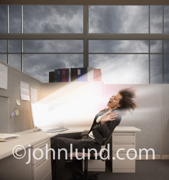 A woman business executive is blown away by the performance of her computer in an office setting.