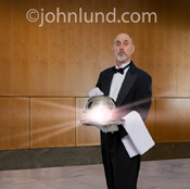 Picture of a butler in a tux with tails and white gloves delivering a domed tray containing a brilliant light symbolizing possibilities, success and service.