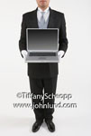 Butler stock photo - A formally dressed butler is standing holding a laptop computer that is open. The butler is wearing a fancy tuxedo and impeccably dressed. Ad pics with butlers.