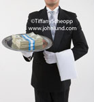A butler is holding a sliver serving tray with stacks of money on the tray. The butler has on white gloves, a tuxedo, and has a white towel draped over his arm. Pic of butler with money.