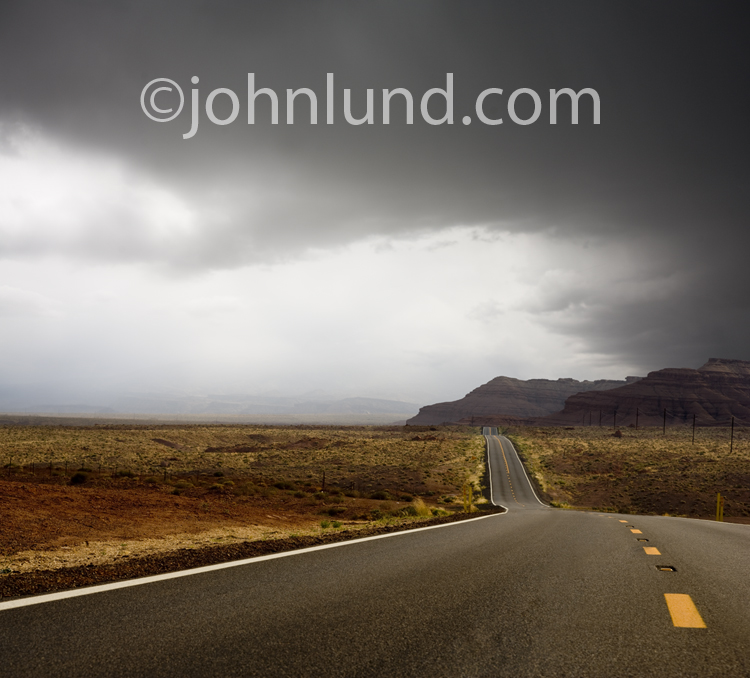 A road stretches into the distance beneath gathering storm clouds in a photo of the calm before the storm.