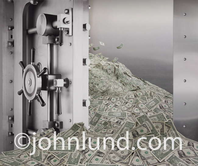 Picture of a open bank vault with cash money pouring out: A stock photo about money, cash flow, capital investment and abundance.