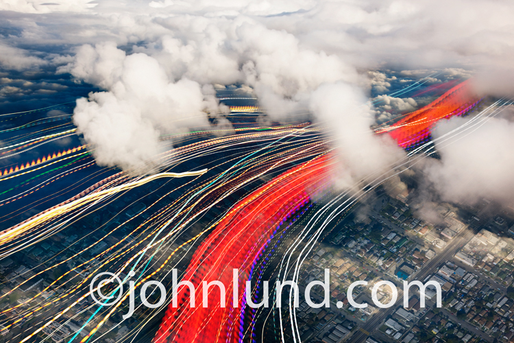 Streaks of colored lights represent the flow of data through the clouds and over an urban terrain below in a concept stock photo about cloud computing,bandwidth and networking.