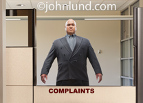A hulking man stands behind the complaint department counter wearing a menacing look in an image about customer service issues.