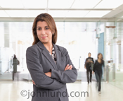Portrait of a smiling confident woman in business apparel in front of what appears to be a shopping mall or other public space.