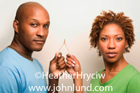 African couple each holding one leg of a wishbone. The attractive couple is about to make a wish and break the wishbone. They are both looking at the camera. He has a blue shirt on and he is bald.  Funny pics for advertising.