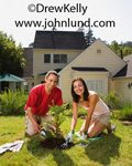 Picture of a couple being green - planting a tree in their back yard.  A middle aged couple, on thier knees planting a young tree in the yard behind their house. Very pretty woman. Handsome couple doing yardwork at home. Gardening pictures.