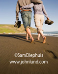 Picture of romantic travel and adventure. Stock photo of a couple walking along the beach barefoot, arms around each others waists.  Pictures of people in love and having fun. Travel and adventure pictures for advertising.