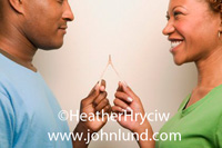 Picture of a couple wishing upon a wishbone.  This black couple is holding a wishbone and are about to break it and see which one gets his or her wish.  Picture useful for ads and advertising. Unique interesting photos.