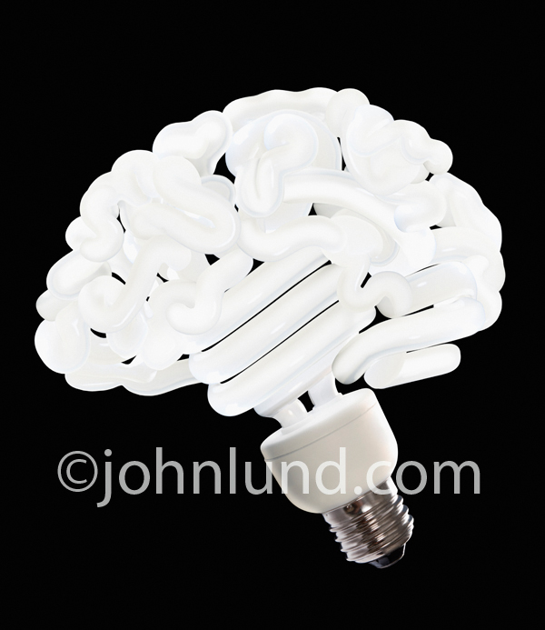 A light bulb stock photo of a twisty bulb shaped like a human brain illustrates the concept of thinking green and creative energy conservation ideas.