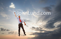 A businessman hangs onto a cluster of light bulbs soaring into the sky in a stock photo about creativity, Imagination and Ideas.