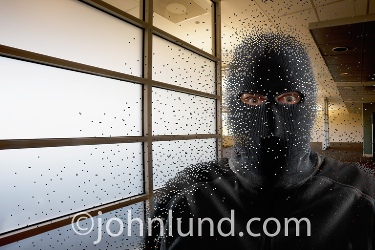 A man wears a ski mask and materializes out of pixels in a cyber crime and hacking photo illustration and stock image.