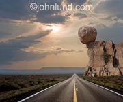 A long road stretches out ahead over a desert landscape and beneath a huge boulder delicately balanced over the highway below.
