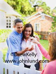 Picture of a woman handing the keys to a new home to a happy young couple.  The new homeowners are standing next to their white picket fence in the yard. Woman handing house keys to happy man with his hand out.