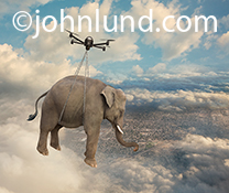 A drone carries an elephant through the clouds high above a city in an image about the power of drones, the unexpected, disruptive technology and transportation and freight issues.