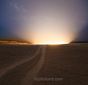 A dirt road leads to a crater spewing out brilliant light ad dusk in an image of the