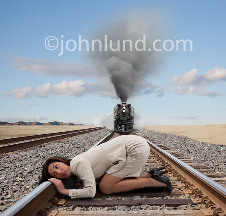 An Hispanic businesswoman has her ear to the tracks oblivious to the steam locomotive bearing down on her in this stock photo about awareness and risk.