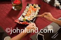 Picture of people eating sushi. Image shows peoples hands using chop sticks to select shushi items from the serving plate. One hand holding chopsticks is male and the other belongs to a woman. Beautiful delicious looking sushi pictures for advertising.