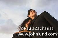 A man and a woman in dark clothing are hugging outside under the gray sky. The camera is down low looking up at the couple.  Unique stock photos of couples outside for ad pics.
