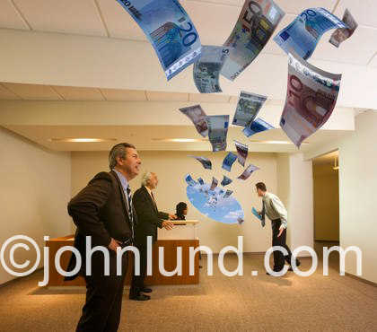 Money flies through an office window in front of office workers; is this flying money (Euros) coming or going?