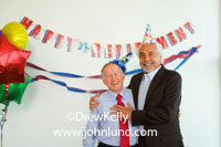 Senior executive reitirement paty pics. Picture of a mature gentleman having his retirment party at work. Decorations on the wall, balloons, streamers, etc. Ad pics for businesses. Two senior men posing for the camera at a retirement party.