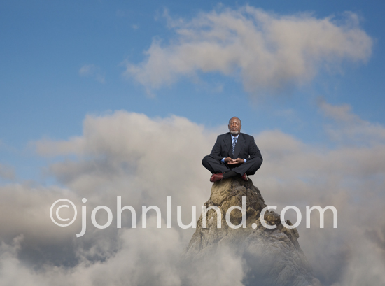 A man sits atop a mountain in a meditation pose while wearing a double breasted business suit.
