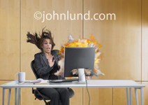 A businesswoman sits at her desk in surprise and shock in front of an exploding computer display.