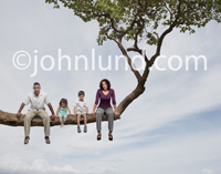 A father, mother and two children sit out on a tree limb in a photograph that symbolizes family risk, danger and adversity including economic and financial difficulties.