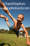 A young boy is being swung around by his dad who has ahold of one leg and one arm.  The boy is quite happy and has a big smile.  The young boy is in a bathing suit and his father is not in the frame.
