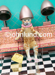 Picture of a cat in a hair salon. The cat has her head under the hair dryer... she had a permanent?  A very funny cat picture.