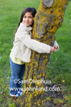 Picture of a cute little girl hugging a tree in the park.  Photo of an adorable young girl in jeans and a coat has her arms around a moss covered tree.  The young grammer school aged girl is smiling and has long brown hair.