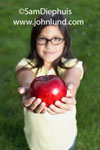 A young school aged girl wearing glasses is holding a big shiny red delicious looking apple out toward the camera. Perhaps she is offering the apple to her teacher?  Pics of a kid with an apple. The young girl is wearing a yellow blouse.