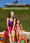 An older woman and her grand daughter are wearing bathing suits and sitting on a beach blanket on a grassy field outside.  The older woman has gray hair and a one piece suit. The young girl has a two piece bikini swim suit.