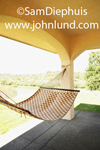 A hammock is tied to the columns on the porch of a spanish style home outside.  The hammock has a checkered design with light and dark brown squares. Bright sunny day.