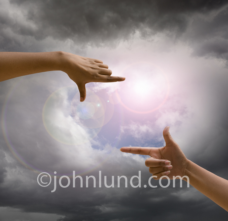 A pair of hands frame the sun breaking out of storm clouds in a stock photo illustrating optimism, the future, and possibilities.