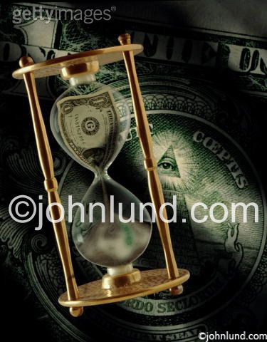 Picture of a dollar squeezing through an hour glass representing time is money for a stock photo. Background is money.