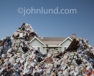 Photo of a house situated in the midst of piles of garbage and refuse in an image about recycling and waste management.