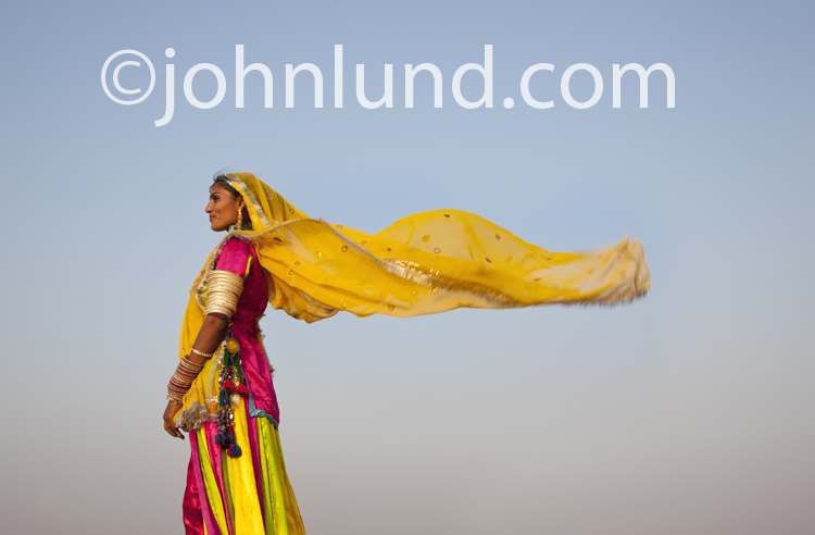 Rajasthan, India: A woman dancer wearing a traditional dance costume stands in the desert with the wind blowing her veil.