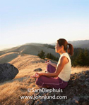 Sitting on a boulder along a rocky ridge a Japanese woman sits alone meditating in the classic lotus yoga position. She has a ponytail and is wearing purple pants and a white shirt.
